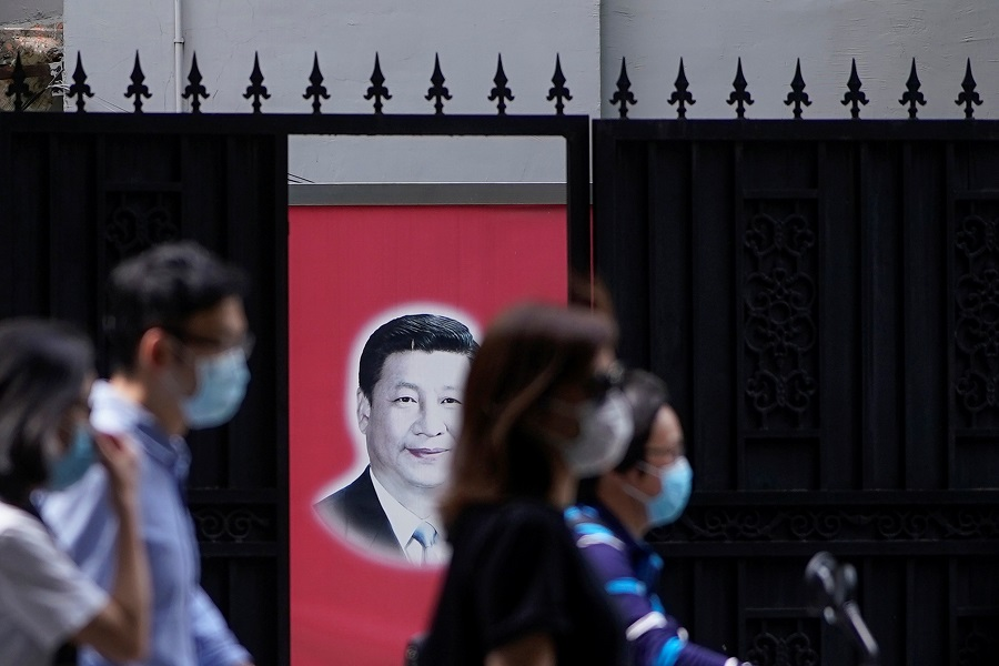 People wearing masks are seen in front of a portrait of Chinese President Xi Jinping on a street on the opening day of the National People's Congress, in China, on 22 May 2020. (Aly Song/Reuters)
