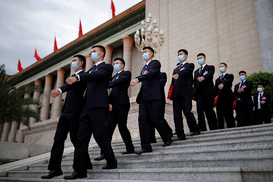 Security personnel wearing masks following the Covid-19 outbreak march outside the Great Hall of the People after the second plenary session of the National People's Congress in Beijing, China, on 25 May 2020. (Thomas Peter/Reuters)
