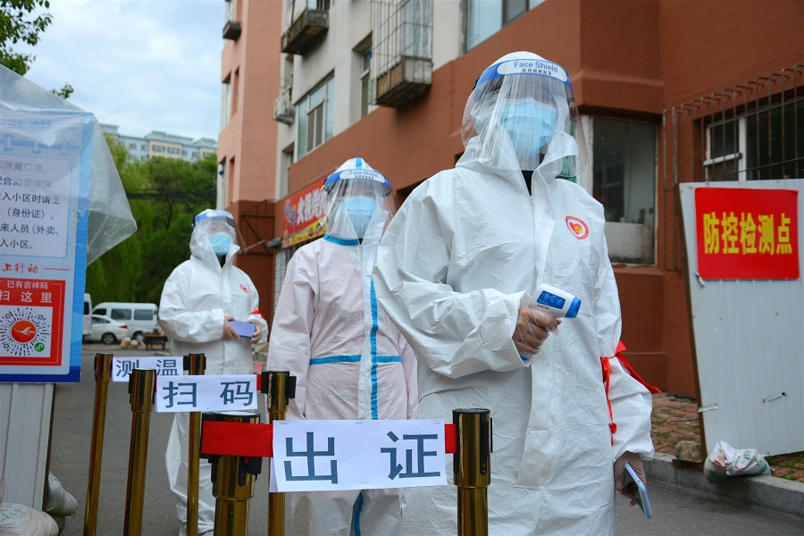 Volunteers in protective suits are seen at a checkpoint at the entrance of a residential compound following the Covid-19 outbreak, in Jilin, China, on 25 May 2020. (China Daily via Reuters)