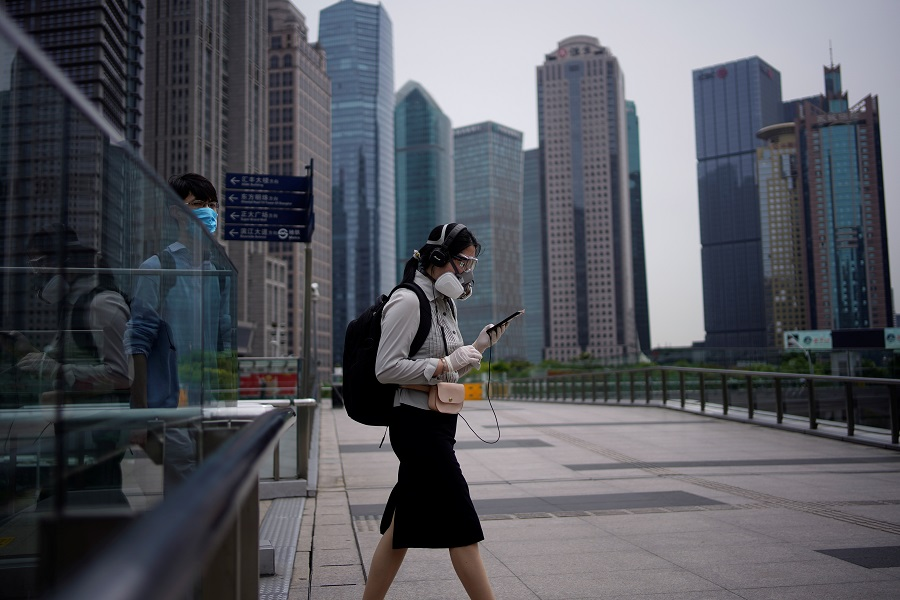 People wearing protective face masks walk past office buildings in Lujiazui financial district in Shanghai, China, on 4 June 2020. (Aly Song/Reuters)