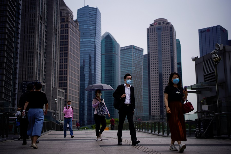 People wearing protective face masks walk past office buildings in Lujiazui financial district in Pudong, Shanghai, on 4 June 2020. (Aly Song/Reuters)