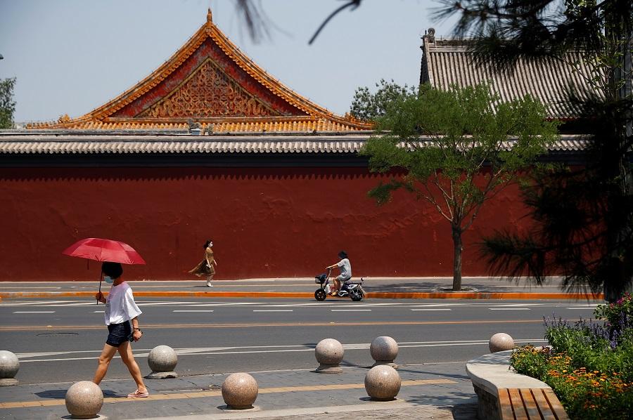 People walk past Lama Temple in Beijing, China, on 19 June 2020. (Thomas Peter/Reuters)