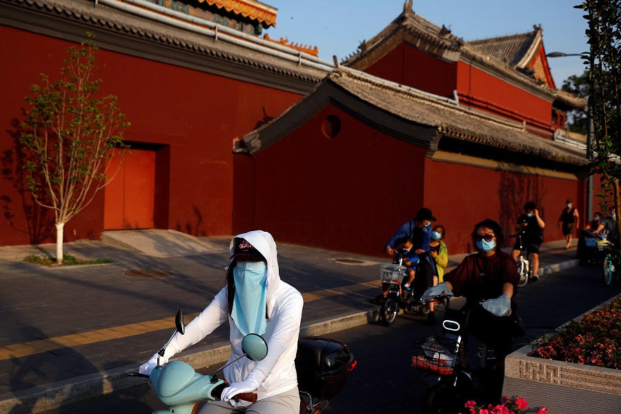 People wearing protective masks ride past Lama Temple in Beijing, China, on 19 June 2020. (Thomas Peter/Reuters)