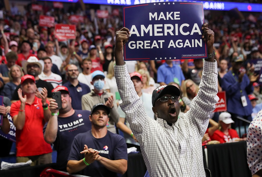 """A supporter of US President Donald Trump holds up a """"Make America Great Again"""" sign as the president arrives at his first re-election campaign rally in several months in the midst of the coronavirus outbreak, at the BOK Center in Tulsa, Oklahoma, US, on 20 June 2020. (Leah Millis/Reuters)"""