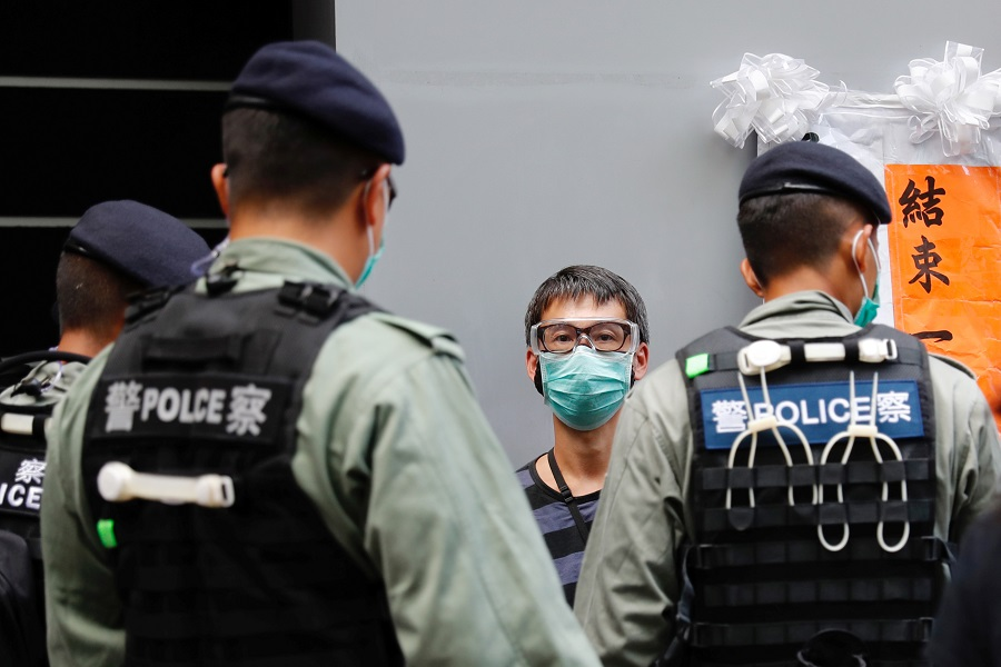 Police search a pro-democracy protester during a demonstration on the anniversary of Hong Kong's handover to China in Hong Kong. REUTERS/Tyrone Siu