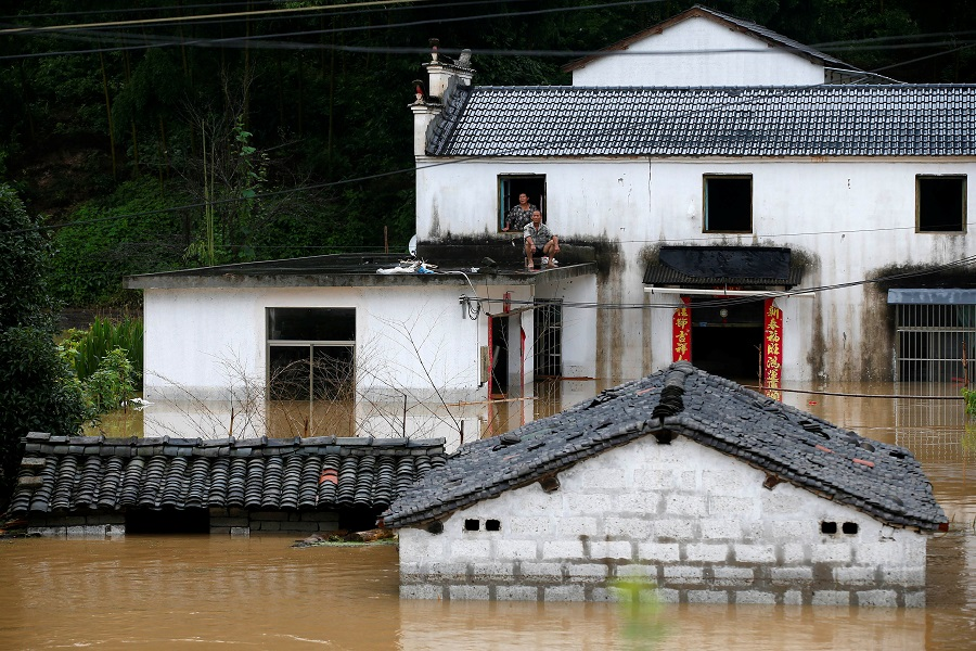 People look on from a house at a flooded village following heavy rainfall in Huangshan, Anhui province, China, on 6 July 2020. (CNS photo via Reuters)