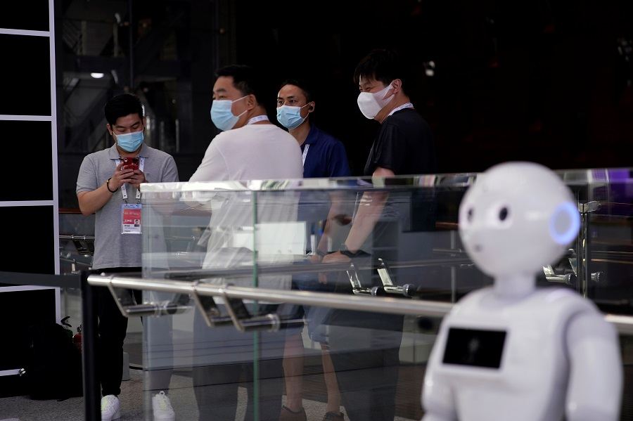 People wearing face masks stand near a robot at the venue for the World Artificial Intelligence Conference (WAIC) in Shanghai, China, 9 July 2020. (Aly Song/Reuters)