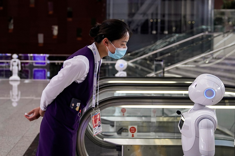 A staff member, wearing a face mask following the Covid-19 outbreak, looks at a robot at the venue for the World Artificial Intelligence Conference (WAIC) in Shanghai, China, 9 July  2020. (Aly Song/Reuters)