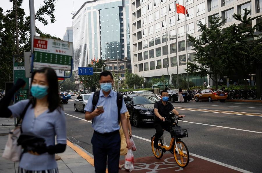 People wearing face masks following the Covid-19 outbreak walk past a Chinese national flag in front of the building of China Securities Regulatory Commission (CSRC) in Beijing, China, on 16 July 2020. (Tingshu Wang/Reuters)