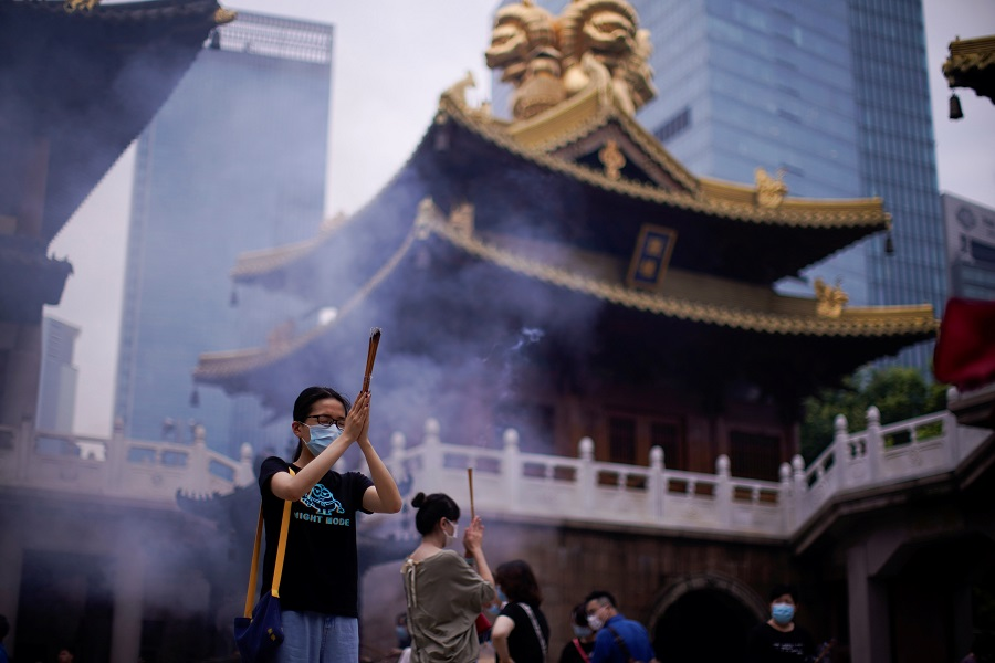 People wearing face masks worship at the Buddhist Jing'an Temple in Shanghai, China, 18 July 2020. (Aly Song/Reuters)