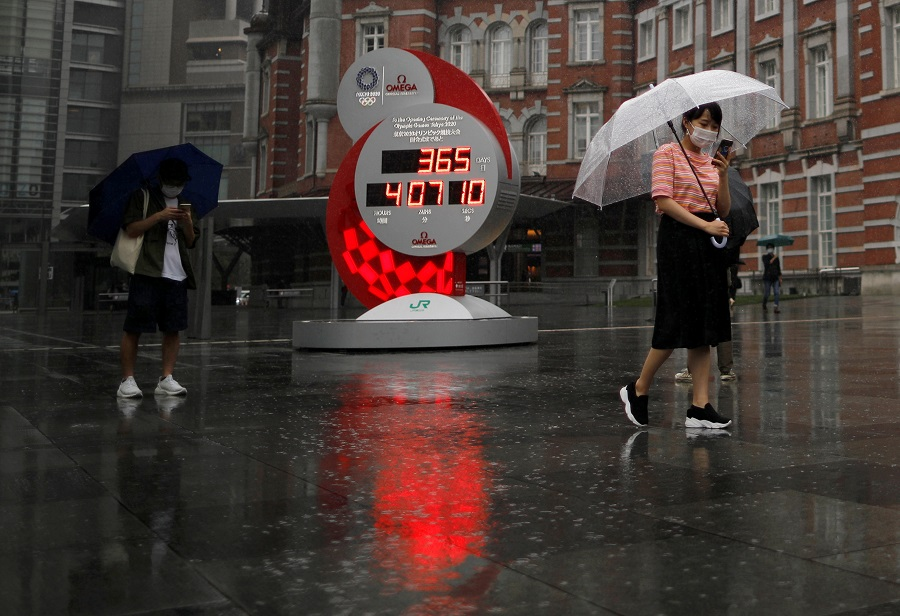 Passersby wearing protective face masks walk past a countdown clock for the Tokyo 2020 Olympic Games that have been postponed to 2021 due to the Covid-19 coronavirus outbreak, in Tokyo, Japan, 23 July 2020. (Issei Kato/Reuters)