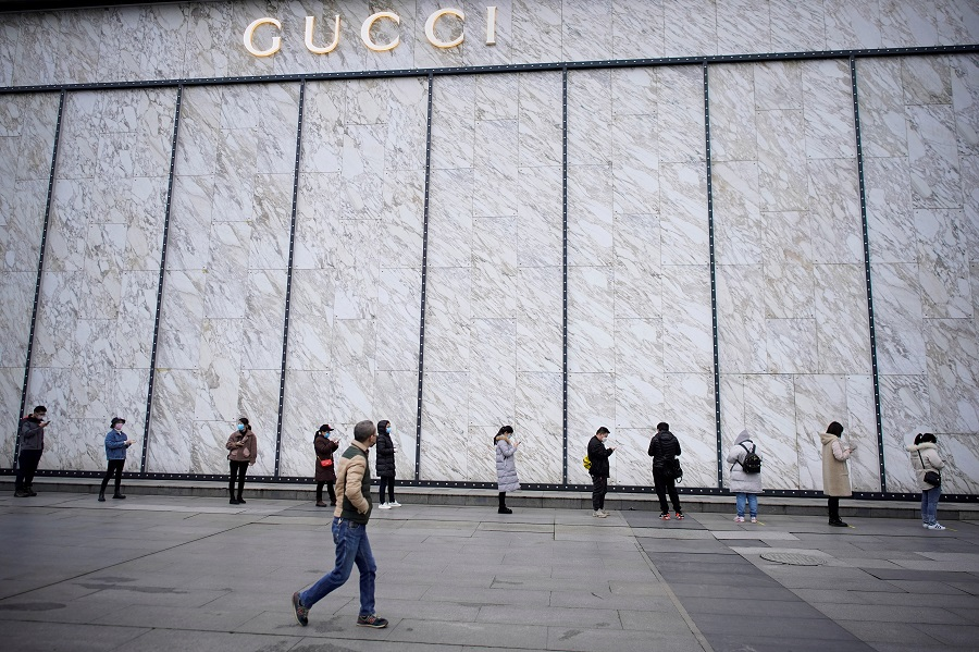 People wearing face masks line up to enter a shopping mall outside a Gucci store in Wuhan, Hubei province, China, on 30 March 2020. (Aly Song/File Photo/Reuters)
