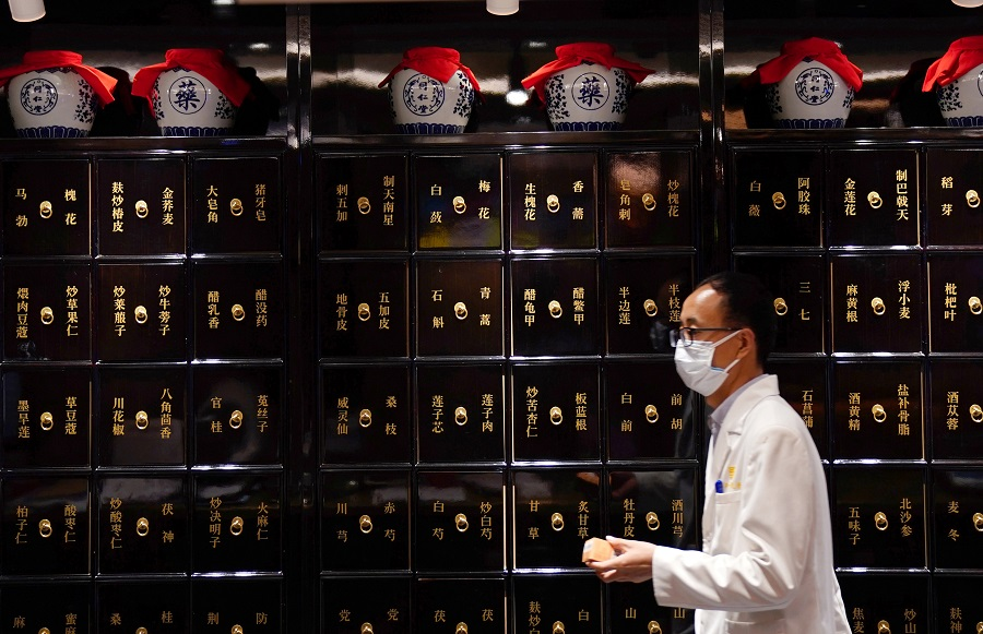 A staff member wearing a face mask following the Covid-19 outbreak walks past cabinets for herbs at Zhima Health store, a cafe and healthcare retail shop owned by the traditional Chinese medicine (TCM) brand Tongrentang, in Beijing, China, on 29 July 2020. (Tingshu Wang/Reuters)