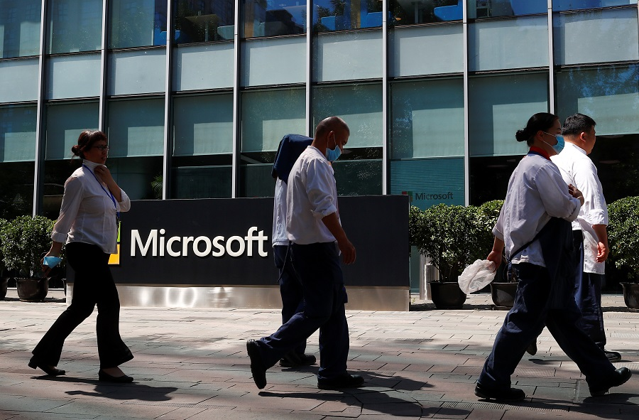 People walk past a Microsoft logo at the Microsoft office in Beijing, China, on 4 August 2020. (Thomas Peter/Reuters)