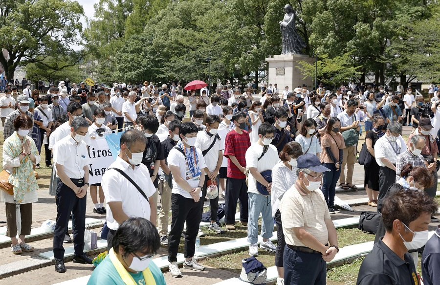 People offer a silent prayers for the victims of the 1945 atomic bombing, during a ceremony commemorating the 75th anniversary of the bombing at Atomic Bomb Hypocenter Park in Nagasaki, Japan in this photo taken by Kyodo, 9 August 2020. (Kyodo via Reuters)