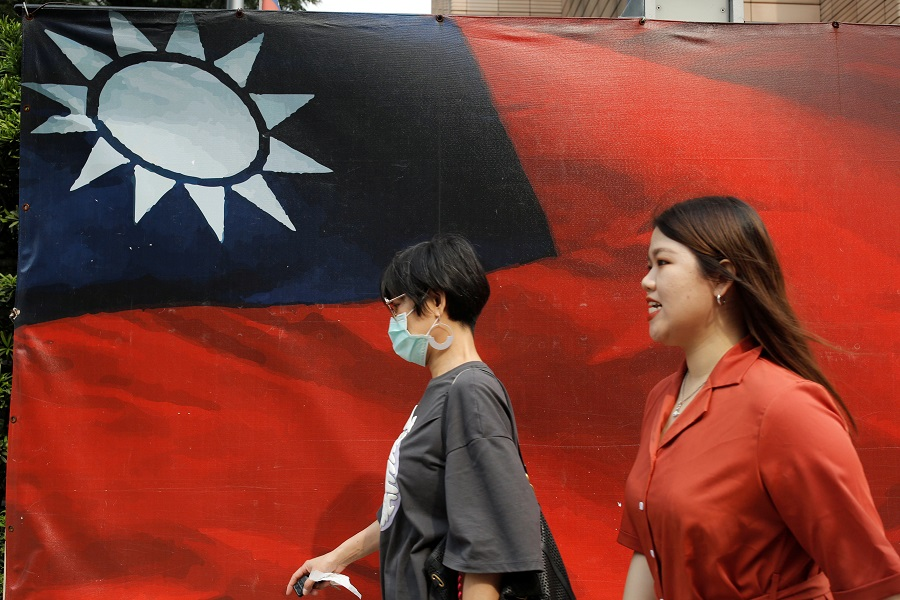 People walk past a Taiwan flag in Taipei, Taiwan, 10 August 2020. (Ann Wang/Reuters)