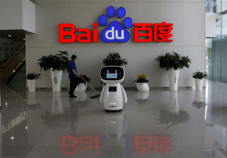 A worker wearing a face mask cleans the floor, near a Baidu AI robot which shows a face mask on its screen, at Baidu's headquarters in Beijing, China, 18 May 2020. (Tingshu Wang/File Photo/Reuters)