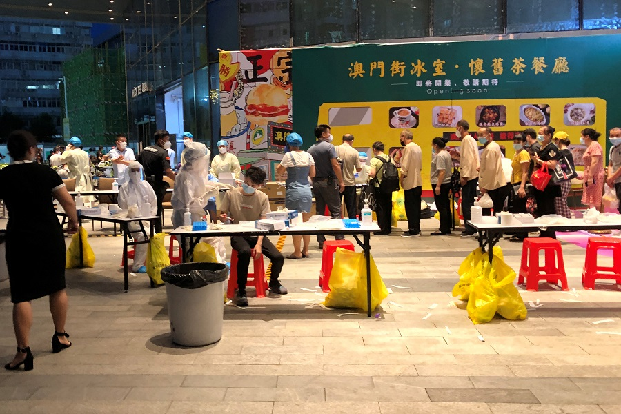 Medical workers wearing protective suits are seen at a nucleic acid testing site outside the IBC Mall in Shenzhen, Guangdong, China, 14 August 2020. (David Kirton/Reuters)