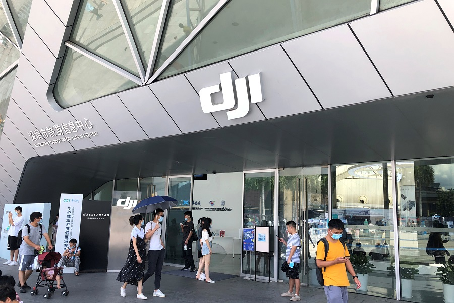 People wearing face masks following the Covid-19 outbreak walk past DJI's flagship store in Shenzhen, Guangdong, China, 8 August 2020. (David Kirton/Reuters)