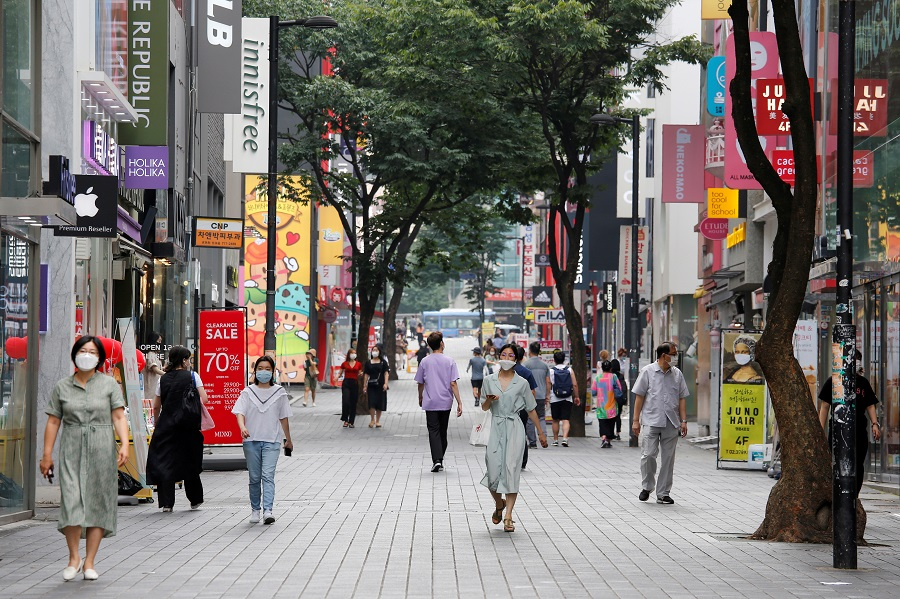 People wearing masks walk at Myeongdong shopping district, in Seoul, South Korea, 19 August 2020. (Heo Ran/Reuters)