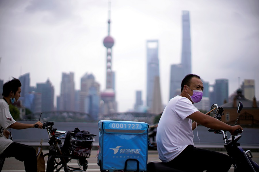 Delivery workers wearing face masks ride scooters in front of Lujiazui financial district, in Shanghai, China, 10 July 2020. (Aly Song/File Photo/Reuters)