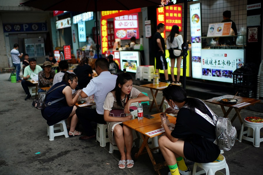 People eat at food stalls on a street in Chengdu, Sichuan, China, 8 September 2020. (Tingshu Wang/Reuters)