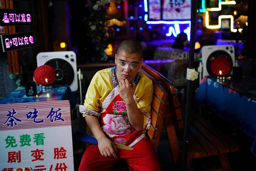 An opera performer waits for customers at a restaurant on Jinli Ancient Street, in Chengdu, Sichuan province, China, 8 September 2020. (Tingshu Wang/Reuters)