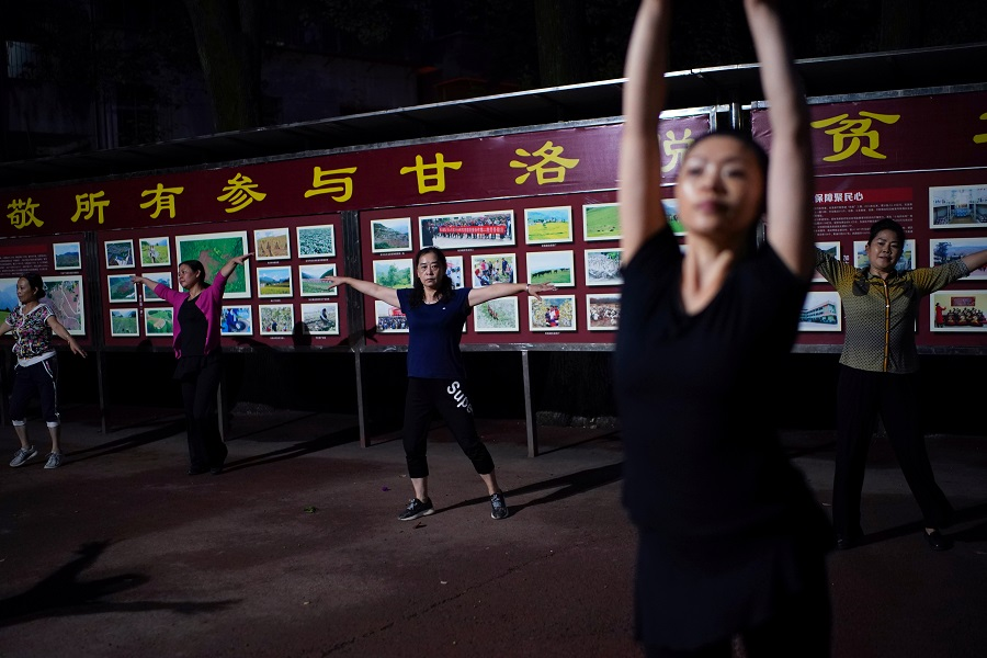 People dance in front of a billboard in praise of people who worked for the poverty alleviation of the county, at a square near the government building in Ganluo county, Liangshan Yi Autonomous Prefecture, Sichuan province, China, 9 September 2020. (Tingshu Wang/Reuters)