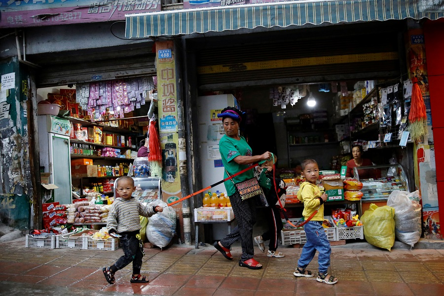 An ethnic Yi woman holds anti-lost straps tied on children's wrists as they walk past shops in Ganluo county, Liangshan Yi Autonomous Prefecture, Sichuan province, China, 10 September 2020. (Tingshu Wang/Reuters)