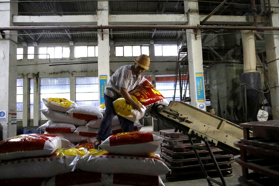 An employee moves a sack of pig feed inside a feed plant of the New Hope Liuhe in Xichang, in Liangshan Yi Autonomous Prefecture, Sichuan province, China, 11 September 2020. (Tingshu Wang/Reuters)