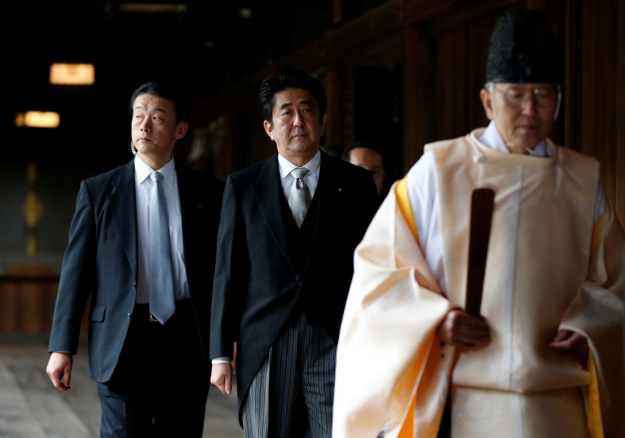 Japan Prime Minister Shinzo Abe (centre) is led by a Shinto priest as he visits Yasukuni shrine in Tokyo, 26 December 2013. (Toru Hanai/File Photo/Reuters)