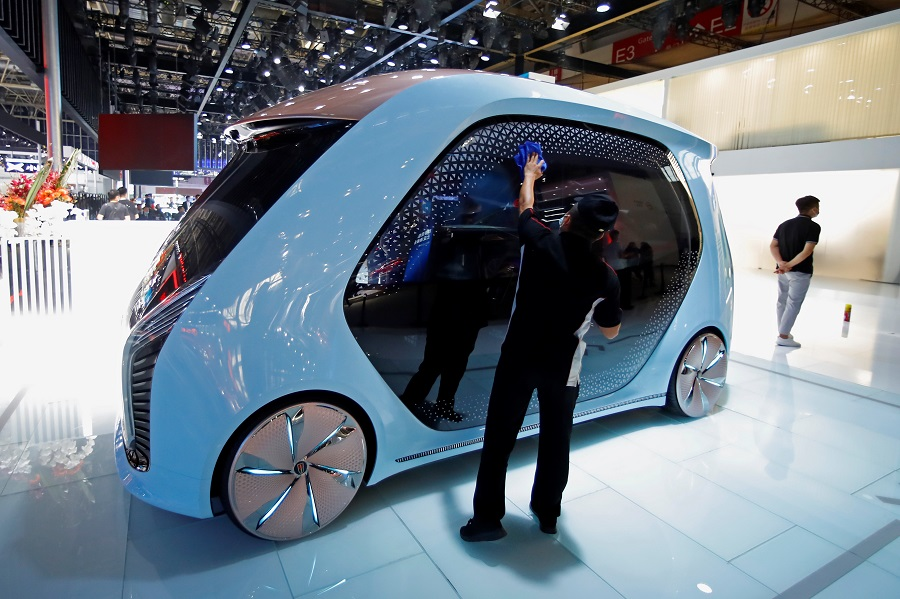 A staff member cleans a Hongqi self-driving concept car at the Beijing International Automotive Exhibition, in Beijing, China, 26 September 2020. (Thomas Peter/Reuters)