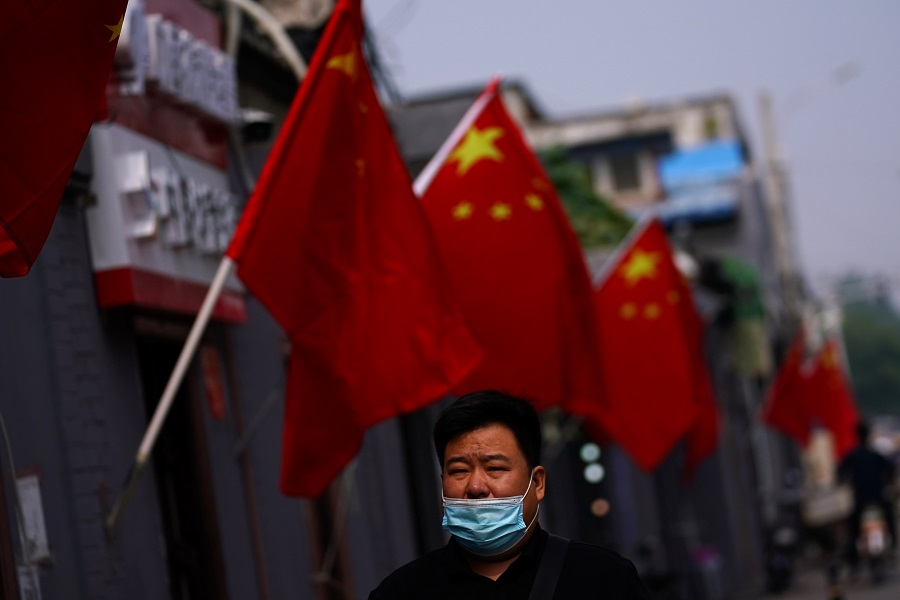 A man wearing a face mask following the Covid-19 outbreak walks past Chinese national flags set up ahead of China's National Day on 1 October in Beijing, China, 28 September 2020. (Tingshu Wang/Reuters)