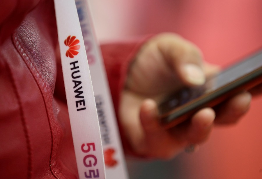An attendee wears a lanyard with the logo of Huawei and a sign for 5G at the World 5G Exhibition in Beijing, China, 22 November 2019. (Jason Lee/File Photo/Reuters)