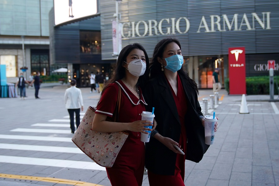 People wearing face masks walk past a Giorgio Armani store at a shopping complex in Beijing, China, 19 September 2020. (Tingshu Wang/Reuters)