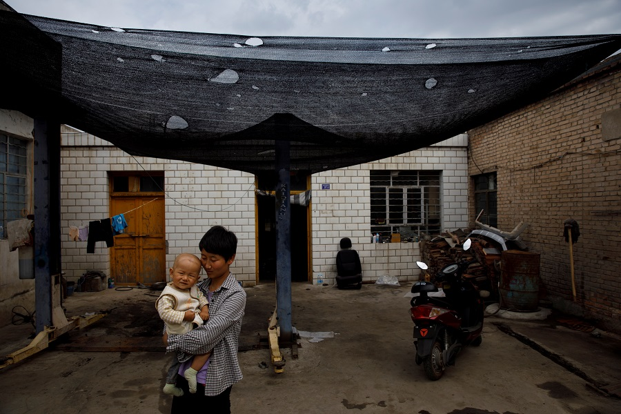 A woman holding her child stands in front of her family's car repair shop opposite the decommissioned Liancheng coal-fired power plant in Heqiao village, Yongdeng county, Gansu province, China, 16 September 2020. (Thomas Peter/Reuters)