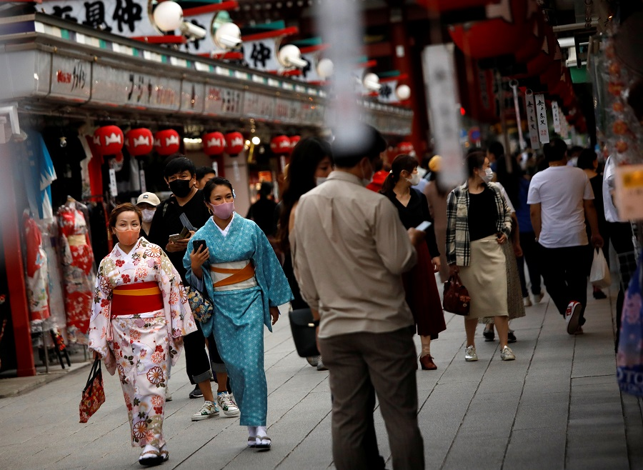Kimono-clad tourists wearing protective face masks walk along Nakamise Street at Asakusa district, a popular sightseeing spot, amid the Covid-19 outbreak in Tokyo, Japan, 13 October 2020. (Issei Kato/Reuters)