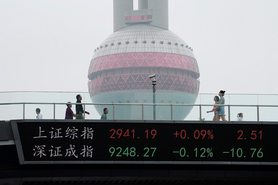 People walk by an electronic board showing the Shanghai and Shenzhen stock indexes, on a pedestrian overpass at Lujiazui financial district in Shanghai, China, 16 May 2019. (Aly Song/File Photo/Reuters)