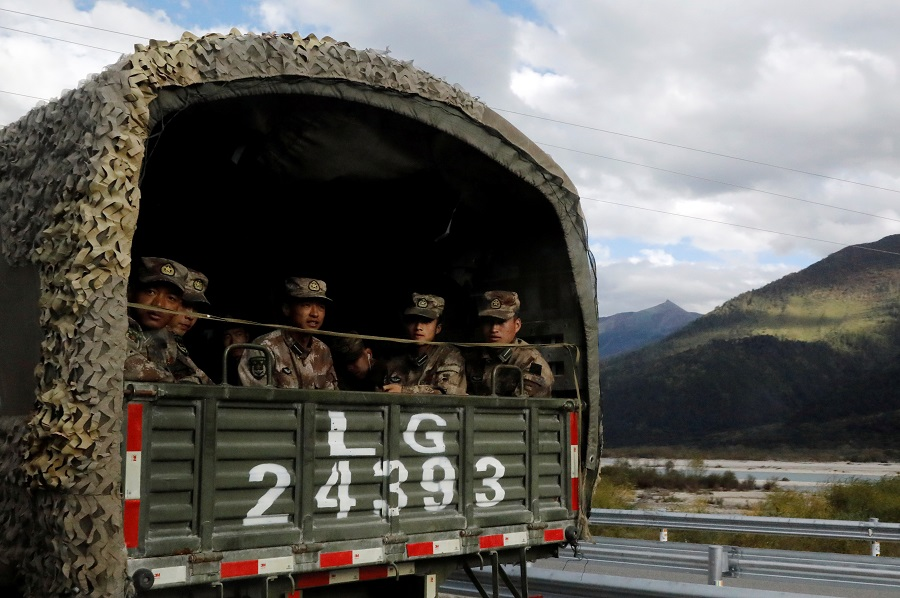 Chinese soldiers of the People's Liberation Army (PLA) sit on the back of a truck on the highway to Nyingchi, Tibet Autonomous Region, China, 19 October 2020. (Thomas Peter/Reuters)