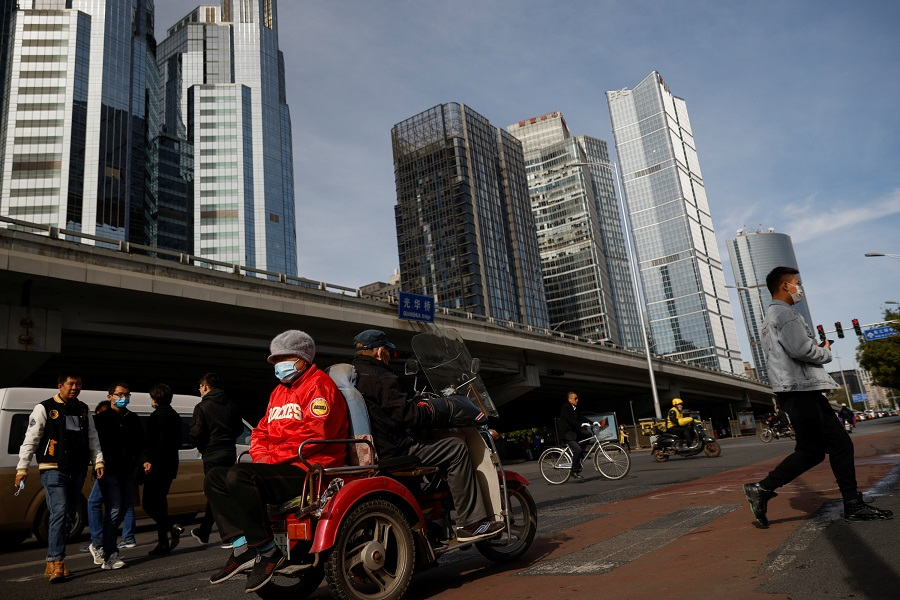 Elderly people cross a street in a tricycle in the Central Business District in Beijing, China, 27 October 2020. (Thomas Peter/Reuters)