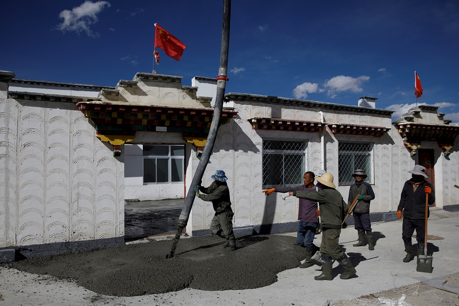 Workers pour concrete on a pavement in the village of Caiqutang, officially created as a relocation site for rheumathritis patients, Damxung county, during a government-organised tour of the Tibet Autonomous Region, China, 16 October 2020. (Thomas Peter/Reuters)