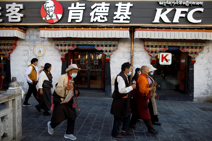 Tibetans walk past a KFC fast food restaurant as they perform a pilgrimage around the Jokhang Temple in Lhasa, during a government-organised tour of the Tibet Autonomous Region to showcase poverty alleviation in China, 15 October 2020. (Thomas Peter/Reuters)