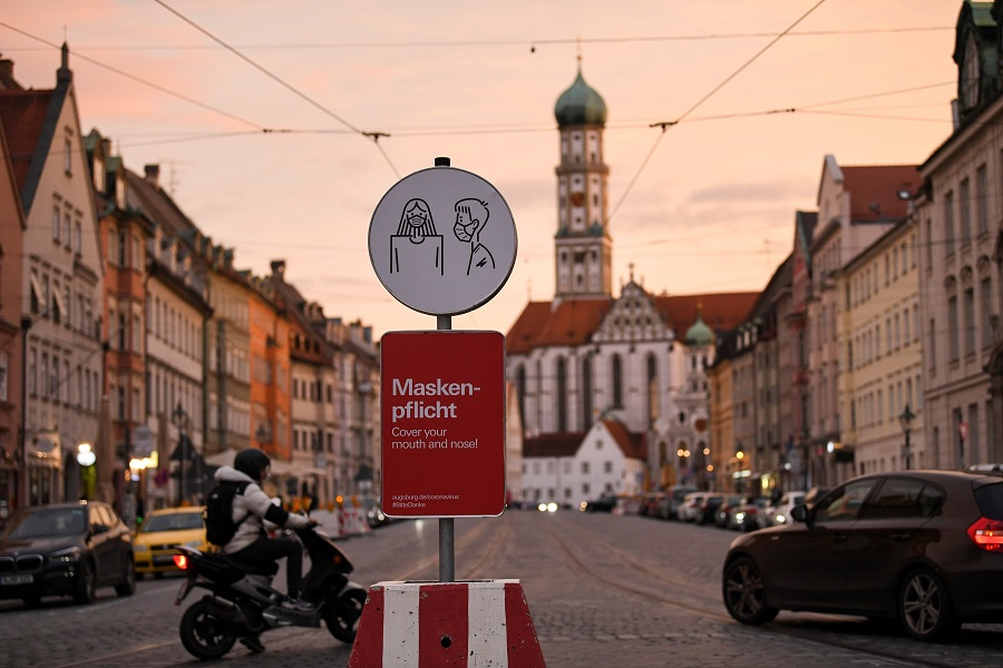 A person drives a motorcycle on a street near a sign that reminds people how to wear a face mask correctly, in Augsburg, Germany, 30 October 2020. (Andreas Gebert/Reuters)