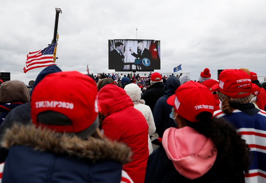 Democratic US presidential nominee Joe Biden and Chinese President Xi Jinping are seen on a screen as supporters of US President Donald Trump gather for a Trump re-election campaign rally in Waterford Township, Michigan, US, 30 October 2020. (Shannon Stapleton/Reuters)