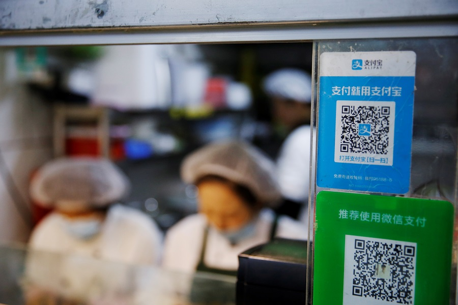 A QR code of digital payment device Alipay by Ant Group, an affiliate of Alibaba Group Holding, is seen next to a QR code of WeChat Pay at a food stall inside a market, in Beijing, China, 2 November 2020. (Tingshu Wang/Reuters)