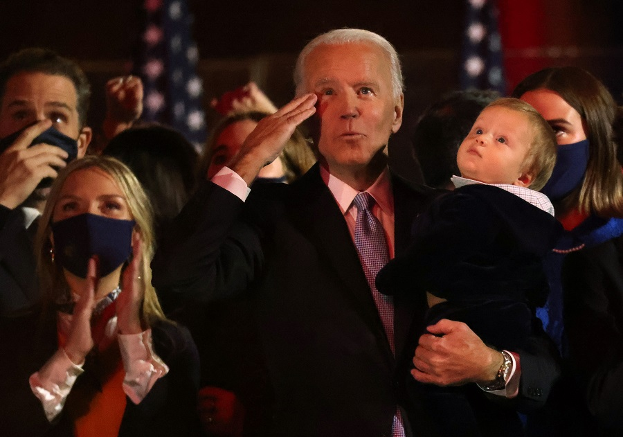 Democratic US presidential nominee Joe Biden gestures as he carries his grandchildren after speaking during his election rally, after news media announced that he has won the 2020 US presidential election, in Wilmington, Delaware, US, 7 November 2020. (Jonathan Ernst/Reuters)