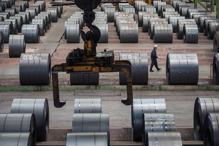 In this file photo taken on 6 August 2018, a worker walks past steel rolls at the Chongqing Iron and Steel plant in Changshou, Chongqing, China. (Damir Sagolj/File Photo/Reuters)