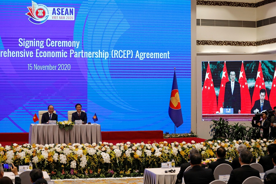 Vietnam's Prime Minister Nguyen Xuan Phuc (left) sits next to Minister of Industry and Trade Tran Tuan Anh as they watch a screen showing Chinese Minister of Commerce Zhong Shan (right) signing next to Chinese Premier Li Keqiang during the virtual signing ceremony of the Regional Comprehensive Economic Partnership (RCEP) Agreement during the 37th ASEAN Summit in Hanoi, Vietnam, 15 November 2020. (Kham/Reuters)
