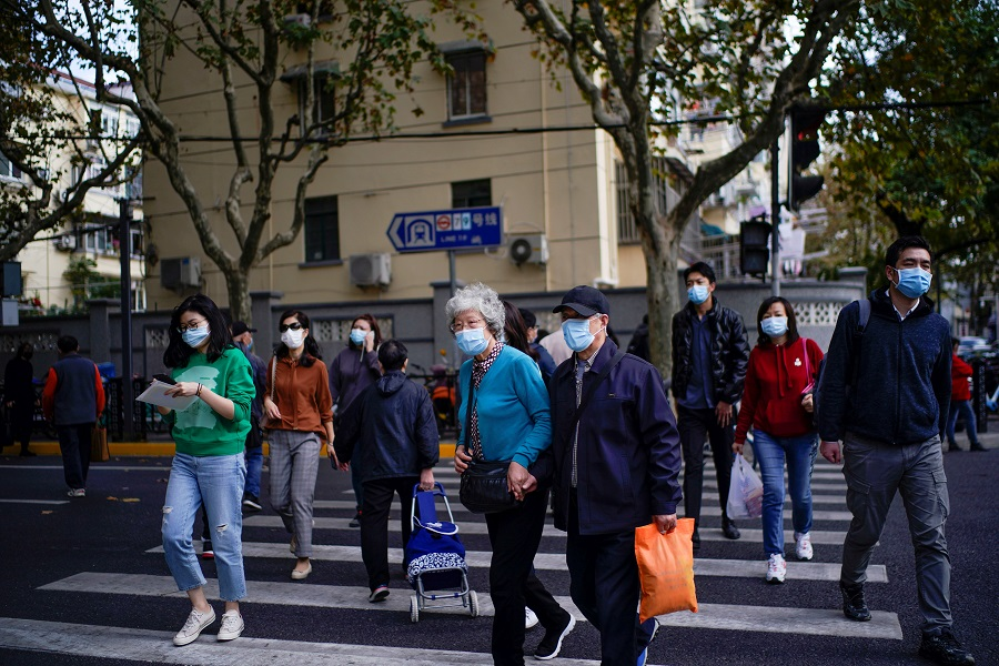 People wearing face masks are seen on a street in Shanghai, China, 18 November 2020. (Aly Song/Reuters)