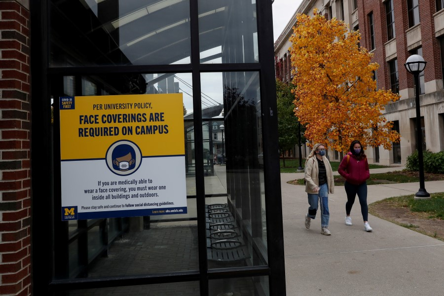 Women with protective face masks walk on the University of Michigan campus, where state health officials in Michigan issued a stay-in-place order for undergraduate students, in Ann Arbor, Michigan, U.S., October 26, 2020. REUTERS/Shannon Stapleton/File Photo